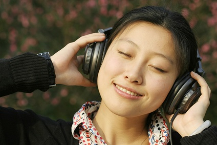 Asian businesswoman listening music