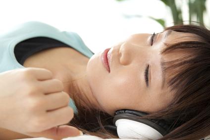 ヘッドフォンで音楽を聴きながら眠る女性